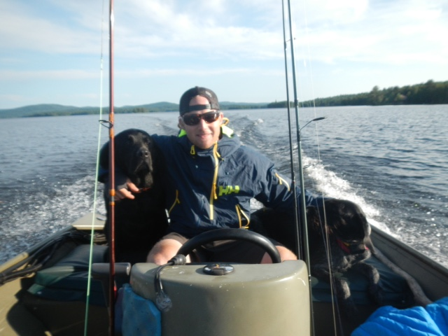 Andrew fishing with black lab on a boat