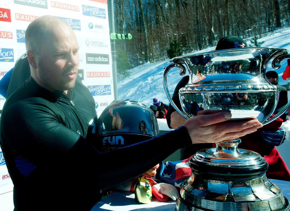 Steve Holcomb touching trophy.