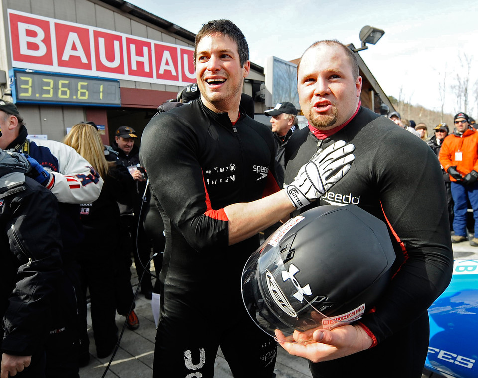Steven Holcomb (R) celebrates with teammate Steve Mesler (L)