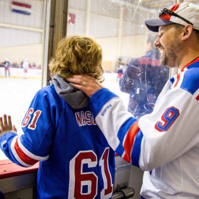 Young boy and his father watching a Ranger's hockey game
